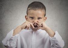 El repugnancia del muchacho en nariz de los pellizcos de la cara algo apesta Foto de archivo libre de regalías