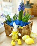 El resorte florece en una pequeños cesta y conejo de pascua Fotografía de archivo libre de regalías