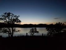 El resplandor caliente de la puesta del sol sobre las aguas que calman fotos de archivo