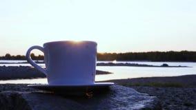 El resplandor de los rayos del sol poniente va al borde de una taza blanca con café caliente Primer a cámara lenta, 1920x1080, hd almacen de metraje de vídeo