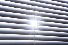 El resplandor solar asteroide brilla a través de persianas de ventana blancas cerradas Imagen de archivo