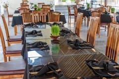 El restaurante del Balinese con las tablas de la disposición, arroz creciente verde claro brota como decoración Bali, Indonesia Imagenes de archivo
