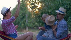 El resto de la familia en jardín, la madre alegre y el padre con el hijo precioso se divierten en la huerta en rayo solar almacen de metraje de vídeo