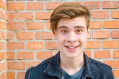 El retrato adolescente de la cara del muchacho que mostraba la expresión excitó sonrisa Imágenes de archivo libres de regalías