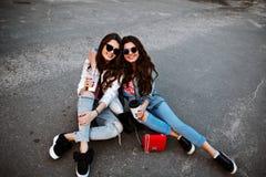 El retrato al aire libre de la forma de vida de la moda de dos mujeres hermosas jovenes, vestido en equipo del dril de algodón, d Fotos de archivo libres de regalías