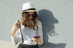 El retrato al aire libre del adolescente en el sombrero, muchacha utiliza smartphone, lee, escribe el mensaje Copie el espacio, f Imagenes de archivo