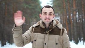 El retrato al aire libre del hombre hermoso en chaqueta está saludando en la cámara almacen de metraje de vídeo