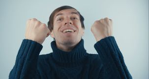 El retrato Amazed sorprendió al hombre joven en suéter negro en el fondo blanco Victoria o éxito súbita Concepto de la victoria almacen de metraje de vídeo