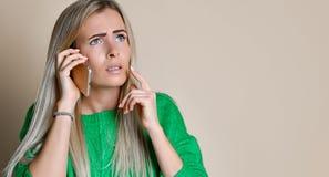 El retrato ascendente cercano de la chica joven en suéter verde mira a un lado y habla en el teléfono digital moderno del artilug foto de archivo