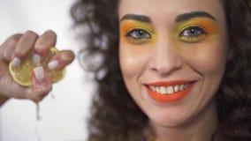 El retrato ascendente cercano de la muchacha rizada joven con brillante compone exprimir el limón amargo con placer y sonrisa Cám almacen de video
