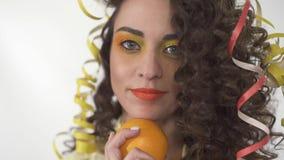 El retrato ascendente cercano de la muchacha sonriente juguetona joven con brillante compone sostener la naranja Cámara lenta almacen de metraje de vídeo