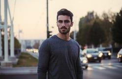 El retrato atractivo del hombre joven en la noche con la ciudad se enciende Foto de archivo libre de regalías