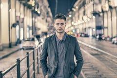 El retrato atractivo del hombre joven en la noche con la ciudad se enciende Imagen de archivo