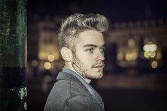 El retrato atractivo del hombre joven en la noche con la ciudad se enciende Foto de archivo