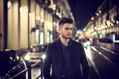 El retrato atractivo del hombre joven en la noche con la ciudad se enciende Imagen de archivo libre de regalías