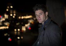 El retrato atractivo del hombre joven en la noche con la ciudad se enciende detrás de él Imagen de archivo
