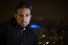 El retrato atractivo del hombre joven en la noche con la ciudad se enciende detrás de él Fotos de archivo