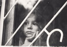 El retrato blanco y negro de la niña triste mira a través de ventana imagen de archivo