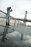 El retrato casual de un hombre joven que presenta delante del ` s de Brooklyn lo va a hacer Foto de archivo