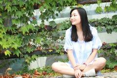 El retrato chino de la mujer hermosa joven se sienta para emparedar en parque Fotografía de archivo libre de regalías