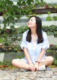 El retrato chino de la mujer hermosa joven se sienta para emparedar en parque Imágenes de archivo libres de regalías