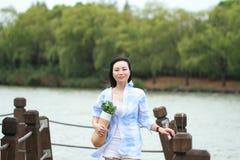 El retrato chino de la mujer hermosa joven ve el lago en parque Fotos de archivo libres de regalías