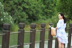 El retrato chino de la mujer hermosa joven ve el lago en parque Fotos de archivo