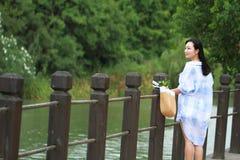 El retrato chino de la mujer hermosa joven ve el lago en parque Foto de archivo