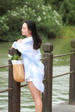 El retrato chino de la mujer hermosa joven ve el lago en parque Imagenes de archivo