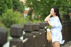 El retrato chino de la mujer hermosa joven ve el lago en parque Fotografía de archivo