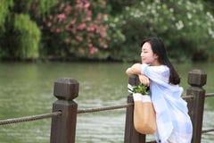 El retrato chino de la mujer hermosa joven ve el lago en parque Imágenes de archivo libres de regalías