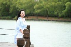 El retrato chino de la mujer hermosa joven ve el lago en parque Fotografía de archivo libre de regalías