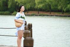 El retrato chino de la mujer hermosa joven ve el lago en parque Imagen de archivo