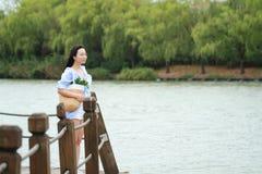 El retrato chino de la mujer hermosa joven ve el lago en parque Imagen de archivo libre de regalías
