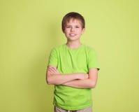 El retrato confiado del muchacho del preadolescente con los brazos cruzó aislado en gre Imagenes de archivo