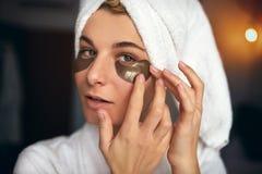 El retrato cosechado de la mujer hermosa con maquillaje natural pone remiendos en el área debajo de los ojos de arrugas y de círc fotos de archivo