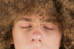 El retrato cosechado de un hombre europeo rizado joven con el pelo rizado largo y los ojos cerrados se cierran para arriba pelo m fotografía de archivo libre de regalías