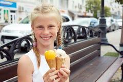 El retrato de 7 años embroma a la muchacha que come el helado sabroso en ciudad Foto de archivo libre de regalías