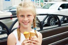 El retrato de 7 años embroma a la muchacha que come el helado sabroso en ciudad Imagen de archivo libre de regalías