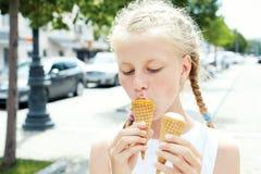 El retrato de 7 años embroma a la muchacha que come el helado sabroso en ciudad Fotos de archivo libres de regalías