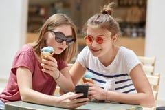 El retrato de adolescentes felices ve las fotos en redes sociales vía el teléfono celular, vestido en camiseta casual y sombras,  Fotos de archivo