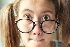 El retrato de casa a la muchacha que se pregunta divertida con las colas de caballo en vidrios Imagenes de archivo