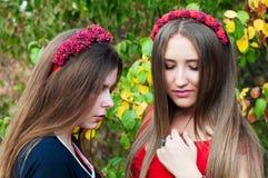 El retrato de chicas jóvenes hermosas se vistió en ornoe y largo rojo Imagenes de archivo
