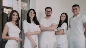 El retrato de dentistas felices, confiados mira la cámara con las manos cruzadas almacen de metraje de vídeo