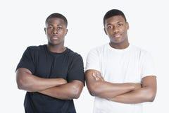El retrato de dos amigos masculinos afroamericanos con los brazos cruzó sobre fondo gris Foto de archivo libre de regalías