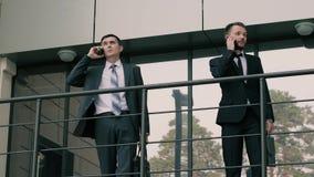 El retrato de dos concentró a los hombres de negocios que hablaban en sus teléfonos sobre trabajo almacen de metraje de vídeo