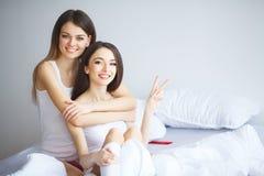 El retrato de dos muchachas alegres hermosas con sonrisas de emisión abraza Fotos de archivo