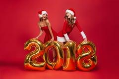 El retrato de dos muchachas felices sonrientes en la Navidad se viste Fotos de archivo libres de regalías
