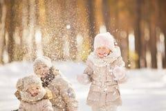 El retrato de dos niñas juega con nieve en invierno Fotografía de archivo