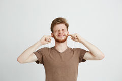El retrato de jóvenes descontentó al hombre enojado con los oídos cerrados de la barba sobre el fondo blanco Imagen de archivo